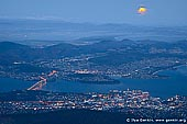 australia stock photography | Moon Rising Over Hobart, Hobart, Tasmania (TAS), Australia, Image ID AU-HOBART-0001. Rising 1270 metre (around 4000 feet) above Hobart's harbour and the wide Derwent River, Mt Wellington in Tasmania. Australia, provides a wilderness experience within 20 minutes of the city and is much loved by locals. The 21 kilometre drive to the summit takes you from temperate rainforest to sub-alpine flora and glacial rock formations, ending in panoramic views of Hobart, Bruny Island, South Arm and the Tasman Peninsula. The interpretation centre at the top protects you from the blustering winds and a viewing platform on the western side of the car park looks out to the southern World Heritage Area beyond. Bushwalking trails suit all fitness levels and barbecue and picnic facilities are provided. Mountain activities also include cycling and abseiling.
