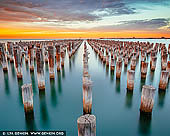 australia stock photography | Sunrise at Princes Pier, Port Phillip Bay, Melbourne, Victoria, Australia, Image ID AU-MELBOURNE-0027. Princes Pier is a 580 metre long historic pier on Port Phillip, in Port Melbourne, Victoria, Australia. It was known as the New Railway Pier until renamed Prince's Pier after the Prince of Wales (later Edward VIII) who visited Melbourne in May 1920. It was opened in 1915 and was able to accommodate the largest of steamers and mail ships. New Railway Pier was renamed Princes Pier in 1921 following the arrival in 1920 of the HMS Renown carrying H.R.H. Edward VIII, Prince of Wales. Over many decades, this pier has played a critical role in commerce, wartime embarkation and migration. With the advent of modern commercial air travel, arrivals to Princes Pier gradually declined from the 1970s. Closed in 1989, Princes Pier has been disused until its recent refurbishment. The redeveloped Princes Pier was launched as a public space in December 2011.