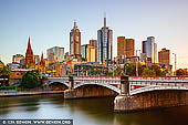 australia stock photography | Melbourne, Princes Bridge and Flinders Street Station at Sunrise, Southbank, Melbourne, Victoria, Australia, Image ID AU-MELBOURNE-0030. Named in honour of HRH the Prince of Wales, later King Edward VII, Princes Bridge is dominated by squat half columns, resting on giant piers, contrasting with its delicate iron girder piers. The bridge's decoration, in typical Victorian era style, includes mouldings and balustrades along the top of the bridge and lamp standings crowning the giant half columns, with the coats of arms of the municipal councils who contributed towards the cost of construction decorating the spandrels. The bridge's abutments, piers and wing walls are made of bluestone quarried from Footscray. The present bridge was built in 1888 and is listed on the Victorian Heritage Register.