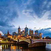 australia stock photography | Melbourne, Princes Bridge and Flinders Street Station at Dawn, Southbank, Melbourne, Victoria, Australia, Image ID AU-MELBOURNE-0035. Melbourne's grandest and oldest Bridge, Princes Bridge was styled on London's Blackfriars Bridge. Listed on the Victorian Heritage Register, Princes Bridge connects St Kilda Road to Swanston Street alongside Flinders Street Railway Station. A bridge has crossed the river at this point since 1845, the present Princes bridge being the third bridge across the Yarra at that location. The first two bridges built in 1845 (timber) and 1850 (stone) were built in response to a population explosion in Melbourne from several hundred to over 80 000 people, caused by the gold rush. In addition to the increase in traffic crossing the bridge, there was also a need to handle increased shipping traffic on the Yarra River and the river was widened to cope with this.