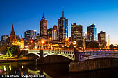 australia stock photography | Melbourne, Princes Bridge and Flinders Street Station at Dawn, Southbank, Melbourne, Victoria, Australia, Image ID AU-MELBOURNE-0041. Princes Bridge, originally Prince's Bridge, is an important bridge in central Melbourne, Australia that spans the Yarra River. It is built on the site of one of the oldest river crossings in Australia. Construction on the new bridge began in 1886 and was completed in 1888 in time for the second International Exhibition to be held in Melbourne. By that time the Yarra River had been heavily modified both upstream and downstream and the major floods of the early years were becoming less common. Constructed by David Munro to a design by Jenkins, D'Ebro and Grainger, it replaced an earlier timber bridge designed by Scottish born bridge designer David Lennox, whose earlier bridges in Sydney include the Lansdowne Bridge and Lennox bridge in Parramatta. John Grainger (1855-1917), the father of the Australian composer Percy Grainger, did the majority of the design work for the bridge, which was opened on 4 October 1888.