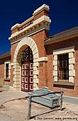 australia stock photography | Old Wentworth Gaol, Wentworth, New South Wales (NSW), Australia, Image ID AU-WENTWORTH-0011. The Old Wentworth Gaol is a small single storey brick gaol with bluestone trim. The entrance is highlighted by a large panelled doorway set in an arch surrounded by stone quoins. The front parapet has a stone corbel trim. The large square windows are surrounded by bluestone quoins. The roof is tiled with slate. The structure is a typical small gaol of the late Victorian period similar to others built in Hay and Gunnedeh. Probably the best example in New South Wales.