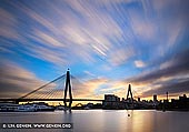 australia stock photography | Anzac Bridge at Sunrise, Glebe, Sydney, NSW, Australia, Image ID AU-SYDNEY-ANZAC-BRIDGE-0012. The Anzac Bridge is a large cable-stayed bridge spanning Johnstons Bay between Pyrmont and Glebe Island near the central business district of Sydney, Australia. The bridge forms part of the Western Distributor leading from the Sydney CBD and Cross City Tunnel to the suburbs of the Inner West and Northern Sydney. The photo made at sunrise on a partly cloudy day when the Sun highlighted clouds in golden hues.