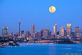 australia stock photography | Full Moon Over Sydney City, New South Wales (NSW), Australia, Image ID AU-SYDNEY-0027. A very large full moon glows in a yellow hue and rises above the Sydney city in New South Wales (NSW), Australia early in the morning right before sunrise. Warm and golden bright sky on East already reflected in skyscraper windows while the sky on West is still cold and blue.