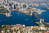 australia stock photography | Sydney City Aerial View, Sydney, NSW, Australia, Image ID AU-SYDNEY-0010. Aerial view photo of Sydney Cove at the Foot of the City. The Sydney Opera House stands out boldly on the harbour. The Royal Botanic Gardens and Government House are behind it and the Harbour Bridge crossing the Sydney Harbour takes you to North Sydney and beyond.