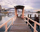 australia stock photography | Lavender Bay Wharf at Dawn, McMahons Point, Sydney, NSW, Australia, Image ID AU-SYDNEY-0025. Soft pastel hues at sunrise the sky over the Lavender Bay Wharf on the McMahons Point in Sydney, NSW, Australia with the Sydney Harbour Bridge in the distance.