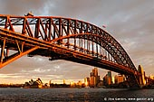 australia stock photography | Sydney Harbour Bridge and Opera House at Sunset, Sydney, New South Wales (NSW), Australia, Image ID AU-SYDNEY-HARBOUR-BRIDGE-0001. A beautiful picture of The Harbour Bridge and The Sydney Opera House at sunset. They are the two most famous Sydney and Australian icons and are well known all over the world. And the wharf near the Luna Park in Milsons Point is one of the best places to photograph the Harbour Bridge. Dark grey paint on the harbour bridge turned vermillion red due to very low sun.