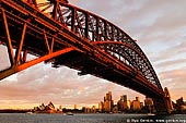 australia stock photography | Harbour Bridge at Sunset from Luna Park, Sydney, New South Wales, Australia, Image ID AU-SYDNEY-HARBOUR-BRIDGE-0004. Silhouette of the beautiful Sydney Harbour Bridge steel arches in Sydney, NSW, Australia. The Sydney Harbour Bridge may not be the longest steel-arch Bridge in the world, but it is the largest and widest. At 48.8 metres (151.3 feet) wide, the Guinness Book of Records lists it as the widest long span Bridge in the world and until 1967, it was Sydney's tallest structure. The Sydney Harbour Bridge was not originally thought of as an arch bridge. Dr. John Job Crew Bradfield initially had a cantilever bridge in mind to span the harbour. However, on a trip to New York he was inspired by the Hell Gate Bridge and he realised the cantilever design was inferior to an arch for his proposed bridge.