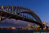 australia stock photography | Harbour Bridge at Sunset from Luna Park, Sydney, New South Wales, Australia, Image ID AU-SYDNEY-HARBOUR-BRIDGE-0008. Dramatic clouds highlighted by sunset, hover above Sydney Harbour Bridge in Sydney, NSW, Australia. This gorgeous scenery was captured from the Larkin Street Lookout in Waverton and it is just one of the elements that attracts visitors to this viewpoint. Watching a sunset can be a peaceful and self-reflecting experience. Many couples like to watch sunsets together as they are often considered a romantic occurrence and have a magical element to them.