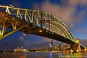 australia stock photography | Sydney Harbour Bridge at Night, Sydney, New South Wales (NSW), Australia, Image ID AU-SYDNEY-HARBOUR-BRIDGE-0009. This is a fantastic view of both the Sydney Opera House and the Harbour bridge on a late summers evening. The great variety of colour comes from the setting sun and the amazing light show that can be seen from the night lighting of the bridge, opera house and city behind.