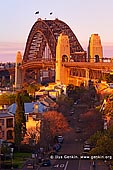 australia stock photography | Sydney Harbour Bridge in the Evening from Observatory Hill, Sydney, New South Wales (NSW), Australia, Image ID AU-SYDNEY-HARBOUR-BRIDGE-0023. Last light of the setting Sun highlighted the iconic Sydney Harbour Bridge while slightly smoky air from recent bushfires in national parks made nice red, orange and yellow glow at the bridge and houses nearby.