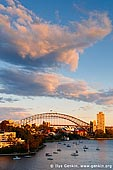 australia stock photography | Sydney Harbour Bridge at Sunset, Waverton, Sydney, NSW, Australia, Image ID AU-SYDNEY-HARBOUR-BRIDGE-0048. Dramatic clouds highlighted by sunset, hover above Sydney Harbour Bridge in Sydney, NSW, Australia. This gorgeous scenery was captured from the Larkin Street Lookout in Waverton and it is just one of the elements that attracts visitors to this viewpoint. Watching a sunset can be a peaceful and self-reflecting experience. Many couples like to watch sunsets together as they are often considered a romantic occurrence and have a magical element to them.