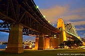 australia stock photography | Sydney Harbour Bridge at Night, Sydney, New South Wales (NSW), Australia, Image ID AU-SYDNEY-HARBOUR-BRIDGE-0012. Sydney Harbour Bridge is international icon for Sydney and Australia. It is  the widest and one of the longest steel arch bridges in the world. The bridge was planned in the early 20th century to span some 500m of harbour between the Sydney CBD and North Sydney, as part of a major upgrade of the Sydney city transportation network, which included the City Circle underground railway. The bridge was designed to take two rail lines from Wynyard Station in the CBD to Milson's Point in North Sydney - as well as six lanes of road traffic, two tram lines and a footpath on each side. After decades of argument and evaluations, onsite works started in July 1923, the main arch began in October 1928, and the structure opened for traffic in March 1932.