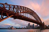 australia stock photography | Sydney Harbour Bridge at Sunset, Sydney, New South Wales (NSW), Australia, Image ID AU-SYDNEY-HARBOUR-BRIDGE-0013. The Sydney Harbour Bridge (Sydney's greatest tourism icon) - on a par with San Francisco's Golden Gate Bridge, New York's Statue of Liberty, London's Tower Bridge and the Eiffel Tower in Paris - took eight years to build and opened in March 1932. It also sometimes known as the 'coat hanger' or simply called 'The Bridge' by Sydneysiders. It has become an Australian icon. Not only is it a symbol of the incredible capabilities of construction, but also the strength and resilience of a nation which had been struck hard by the Depression and which found inspiration in the magnificent structure before them. The iconic Sydney Harbour Bridge spans the harbour at its narrowest point between Dawes and Milsons Points, where you see the bridge and the Sydney Opera House.