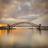 australia stock photography | Sydney Harbour Bridge at Sunrise Before Storm, A View from Blues Point Reserve, Sydney, New South Wales (NSW), Australia, Image ID AU-SYDNEY-HARBOUR-BRIDGE-0044. Changing weather conditions like approaching storm can create dramatic light. Bad weather is, by it's very nature, unpredictable. But great light can appear, either side of a weather front, and transform the landscape in most remarkable ways. You need to be there, properly attired, with your camera ready as these truly serendipitous moments are fleeting. Patience and a willingness to gamble on the result is also necessary. This photo of the the Sydney Harbour Bridge and the Opera House was created at sunrise right before the storm hit Sydney. The magnificent light lit the sky for only a couple of minutes and then gone leaving the sky dull and flat.