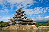 japan stock photography | Black Matsumoto Castle, Matsumoto, Nagano Prefecture, Chubu region, Honshu Island, Japan, Image ID JP-MATSUMOTO-0001. Stock image of the Black Matsumoto Castle (Matsumoto-jo) in Matsumoto, Nagano Prefecture of Japan made on a beautiful and clear sunny morning with nice white clouds in the blue sky. It is a perfect time to have a stroll or a walk along Matsumoto castle moat under lush green trees.