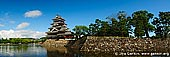 japan stock photography | Panoramic View of the Matsumoto Castle, Matsumoto, Nagano Prefecture, Chubu region, Honshu Island, Japan, Image ID JP-MATSUMOTO-0009. Wide panoramic view of the black Matsumoto Castle (also known as 'Crown Castle') in Matsumoto, Nagano Prefecture of Japan with castle moat in front and nice blue sky above.