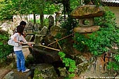 japan stock photography | Visitors Cleanse Their Hands at a Purification Fountain, Daisho-in Temple, Miyajima, Honshu, Japan, Image ID JPMI0061.