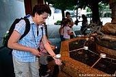 japan stock photography | Woman Cleanse Her Hands at a Tsukubai (Purification Wash Basin), Senso-ji Temple, Asakusa, Tokyo, Kanto Region, Honshu Island, Japan, Image ID JP-TOKYO-0010.
