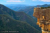 landscapes stock photography | Kanangra Walls, Kanangra-Boyd National Park, New South Wales (NSW), Australia, Image ID AU-KANANGRA-BOYD-NP-0002. Woman is standing on the edge of the Kanangra Walls cliffs in the Kanangra-Boyd National Park in New South Wales (NSW), Australia overlooking canyons and mountain ranges covered in blue mist from eucalyptus.