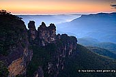landscapes stock photography | The Three Sisters, Echo Point, Katoomba, Blue Mountains, NSW, Australia, Image ID THREE-SISTERS-BLUE-MOUNTAINS-0001. The Three Sisters towering above the Jamison Valley at Sunrise as it was seen from the Echo Point in Katoomba in Blue Mountains, NSW, Australia. The lighter coloured orange and yellow sections indicate fresh rock, exposed by recent erosion.