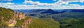 landscapes stock photography | The Three Sisters Panorama, Echo Point, Katoomba, Blue Mountains, NSW, Australia, Image ID THREE-SISTERS-BLUE-MOUNTAINS-0005. The Three Sisters are an unusual rock formation in the Blue Mountains of New South Wales, Australia, on the north escarpment of the Jamison Valley. They are close to the town of Katoomba and are one of the Blue Mountains' best known sites, towering above the Jamison Valley. Their names are Meehni (922 m), Wimlah (918 m), and Gunnedoo (906 m). The commonly told legend of the Three Sisters is that three sisters, Meehni, Wimlah and Gunnedoo, lived in the Jamison Valley as members of the Katoomba tribe. They fell in love with three men from the neighbouring Nepean tribe, but marriage was forbidden by tribal law. The brothers were not happy to accept this law and so decided to use force to capture the three sisters. A major tribal battle ensued, and the sisters were turned to stone by an elder to protect them, but he was killed in the fighting and no one else could turn them back. This legend is claimed to be an Indigenous Australian Dreamtime legend.
