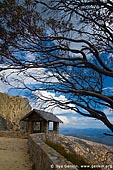 landscapes stock photography | Old Stone Hut and View over Australian Alps from The Horn, Mount Buffalo National Park, Victoria, Australia, Image ID MOUNT-BUFFALO-VIC-0008. Vertical image of the old rock built hut nicely surrounded by a curved dry tree at the starting point of the Horn mountain summit walking in Mount Buffalo National Park, Victoria Hight Country, Australia. This viewpoint offers great view over Australian Alps for all tourists and visitors.