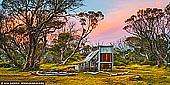 landscapes stock photography | Wallace's Hut at Sunset, Falls Creek, Victoria, Australia, Image ID AU-FALLS-CREEK-WALLACES-HUT-0004. Wallace's hut was built in 1889 and is probably the oldest surviving hut on the high plains of north-east Victoria. It was built in six weeks by Irish immigrant brothers Arthur, William and Stewart Wallace among old snow gums on a grassy plain above the snowline. The brothers held grazing leases on the High Plains and the hut was built to provide shelter for the cattlemen working there. The timber was cut from the forest about four hundred metres east of the hut, and the hearth stone was dragged in from Pretty Valley. The chimney had a base of rubble and above this iron sheeting on a timber frame. The slab walls were lined with hessian and later with tar-paper, and inside there was a bush table, sleeping platform and a rustic fire-side settle. The hut was used by many local cattlemen, as well as stockmen from New South Wales, who brought sheep here during the 1914-18 drought. Many such huts were built in mountain areas, but they were flimsy structures, and at great risk from bush fires, and no others have survived from the nineteenth century. The State Electricity Commission used the hut from the late 1920s until the early 1940s to collect data on precipitation for possible future hydroelectric works, and SEC employee Joe Holsten covered the roof and later the walls with corrugated iron, renewed the chimney and added a skillion for storing firewood and horse feed. In the 1940s the Rover section of the BoyScout Association took over responsibility for maintenance and it became an important refuge and destination for walkers and skiers.