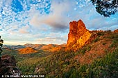 landscapes stock photography | Belougery Spire at Sunset, Warrumbungle National Park, New South Wales (NSW), Australia, Image ID AU-WARRUMBUNGLES-0005. The Warrumbungle National Park region was discovered by Europeans in 1818 by John Oxley while looking for an inland sea. The name of the mountain range, 'Warrumbungle,' means crooked mountains in the local Kamilaroi Aboriginal language. There is evidence of Aboriginal use and known occupation sites within the park. The idea of a reserve to conserve the area of the Warrumbungles was first entertained by the National Parks and Primitive Areas Council in 1936, with the first area being conserved in 1953. The national park takes up some 23 000 hectares, 33km west of Coonabarabran and 90km north of Gilgandra. More areas are to be added to the park in the future. It is a park of rocky spires, ridges, domes and gorges. The rocky peaks include the famous Breadknife, Bluff Mountain and Grand High Tops, which are an extremely popular destination for bush walkers.