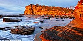 landscapes stock photography | The Skillion at Sunrise, Terrigal, Central Coast, NSW, Australia, Image ID SKILLION-TERRIGAL-0001. Terrigal is a popular residential, tourist and retirement centre with a bustling holiday ambience which is modified by the gracious Norfolk pines along The Esplanade, the pleasant beach front walkway which heads south to Broken Head, and the dominating natural feature known as 'The Skillion' which offers dramatic views up and down the coast. Visitors are attracted by the town's classy four and a half star hotel, the fishing, swimming, surfing, boating and the coastal scenery. Terrigal Beach is one of those glorious beaches which stretches, unbroken, for four kilometres and is known as Terrigal at the southern end and Wamberal at the northern end. The Skillion is the most prominent landmark of the region, with a steep cliff facing the ocean rising to a convenient lookout area that is easily accessed by a flat grassy area leading up from the reserve.