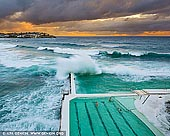 landscapes stock photography | Waves Crushing at Bondi Icebergs, Bondi Beach, Sydney, NSW, Australia, Image ID AU-BONDI-BEACH-0006. Huge waves crashing over the swimming pools at the Bondi Icebergs Club on a beautiful morning in Sydney, NSW, Australia. Sydney's most famous beach is Bondi. At its southern end is Bondi Baths or Bondi Icebergs swimming pool, an eight-lane, 50-meter saltwater pool built into the cliffs. Open every day except Thursdays, it is home to the Bondi Icebergs Club, which was founded in 1929 by a small group of friends. To become an Icebergs member you must swim three of every four Sundays for five years during the winter (May to September Down Under). It is a true test of dedication, for while outsiders might think that Australia is the land of endless summer, in winter the ocean water is teeth-chattering cold. And on opening day of the winter swimming season, it is tradition that lumps of ice are tossed into the pool to test the hardiness of the competitors.