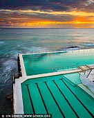 landscapes stock photography | Sunrise at Bondi Icebergs, Bondi Beach, Sydney, NSW, Australia, Image ID AU-BONDI-BEACH-0004. The Icebergs Bondi Baths have been a landmark of Bondi Beach for over 100 years. For more than a century, Tasman Sea waves have crashed against - and into - the Bondi Baths, an Olympic-size pool that became the home of the Bondi Icebergs, a winter swimming club, in 1929. Because of its solid concrete construction, the pool is always slightly colder than the ocean, even though it uses the same water. The public is welcome here, but locals who want to become Icebergs (i.e., earn their official stripes as winter swimmers) must log 75 swims here during what most would consider the 'off-season' (when pool temps dip below 15C in wintry July). Casual visitors favour summertime dips, when the water warms to the high 20s by February. Upon emerging from the striking shoreside pool at the Icebergs, bathers enjoy the amenities of its modernist, beachy clubhouse complex, which includes a gourmet bistro, two bars, fitness facilities and a 1,600-square-foot sundeck.