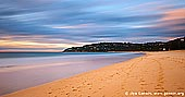 landscapes stock photography | Palm Beach at Sunrise, Palm Beach, Sydney, NSW, Australia, Image ID PALM-BEACH-BARRENJOEY-0003. This view of sandy Pacific coastline was taken at sunrise and it shows Palm Beach of the Sydney's Northern Beaches, Australia. Colours of yellow and pink stream across moving clouds in the morning sky.