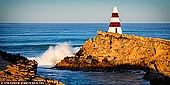 landscapes stock photography | Waves Crushing at Obelisk, Robe, Limestone Coast, South Australia, Australia, Image ID AU-ROBE-0002. Robe in South Australia is a small town fishing port with a population of about 1,500 people. The town was named after Major Frederick Robe, which founded the area as a shipping port in 1845. During the gold rush era of 1857 thousands of Chinese immigrants landed at Robe on destination to Ballarat and Bendigo. Robe attracts many tourists seeking a seaside holiday. Long Beach is a popular beach for swimming, surfing and fishing. Long Beach is also one of Australia's few beaches left where you can still drive your vehicle along the beach due to its firm sand composition. The rugged rocky cliffs around Robe also provide ideal fishing and diving conditions. The best spots to fish include Rock fishing in Guichen Bay, wharf fishing at Lake Butler Boat Haven Channel or surf fishing between Long Gully and West Beach. A great attraction to Robe is the Obelisk shipping marker found at Cape Dombey. It was built in 1855 and stands 12m (40 ft) high and is 30m (100 feet) above sea level. The noticeable red and white bands help guide mariners when boating.
