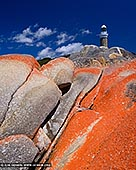 landscapes stock photography | Eddystone Point Lighthouse #2, Mount William National Park, Tasmania (TAS), Australia, Image ID TAS-EDDYSTONE-POINT-LIGHTHOUSE-0002. Photograph of the Eddystone Point Lighthouse with lichen covered rocks in foreground. On the far north-east of Tasmania, almost on the 41 st latitude, is the Eddystone Point Lighthouse. It is a magnificent circular stone 36 metre high tower, built of locally quarried granite and is situated on the headland known as Eddystone Point 41 metres above sea level. The light commenced operation on 1 May 1889. Eddystone Point LighthouseThe light was established because of nearby dangers in eastern Banks Strait and south along the coast known as the Bay of Fires. Georges Rocks, Victorias Rocks and Black Reef are amongst the more prominent dangers in the area.