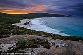 landscapes stock photography | Cable Beach at Sunrise, Torndirrup, Western Australia (WA), Australia, Image ID AU-WA-ALBANY-CABLE-BEACH-0001. Cable Beach, next to The Gap and Natural Bridge, is rough and treacherous. There is a giant boulder in the middle of the Cable Beach which was lifted by the force of the waves and placed onto the stones. It's a wonderful, dramatic beach to walk along but most days it's far too dangerous for swimming. It has a lot of rocks and reef close to shore and pummelled by huge waves. Cable Beach is accessible only by a descent which may also be referred to as a bit of a hike! The staircase descends from the carpark onto the rocky boulders which continue for at least twice as long as the stairs down onto the beach.