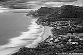 landscapes stock photography | Stanwell Park from Bald Hill Lookout, Illawarra, New South Wales (NSW), Australia, Image ID AU-STANWELL-PARK-0001. Black and white view from Bald Hill Lookout over Stanwell Park valley to Mount Mitchell, and the site of the Sea Cliff Bridge in the background. Stanwell Park is a picturesque coastal village and northern suburb of Wollongong, NSW, Australia. It is the northernmost point of the Illawarra coastal strip and lies south of Sydney's Royal National Park. It is situated in a small valley between Bald Hill to the north, Stanwell Tops to the west and Mount Mitchell to the south. It has two lagoons from the village's two creeks, Stanwell and Hargrave Creeks, and a beach running between headlands. Bald Hill is one of Illawarra, Australia's best known and most popular lookouts, situated atop the hill of that name. Not only are the views excellent, the area is also internationally known as a major hang gliding centre.