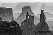 landscapes stock photography | Washer Woman Arch, Monster Tower and Airport Tower, Island in the Sky, Canyonlands National Park, Utah, USA, Image ID CANYONLANDS-NATIONAL-PARK-UTAH-USA-0006. Washer Woman Arch, Monster Tower and Airport Tower cast shadows on haze in the air at sunrise in the Island in the Sky district of Canyonlands National Park, Utah, USA. Washer Woman Arch resembles a woman washing clothes on an old-fashioned washboard. The Washer Woman Arch is in silhouette in front of the Airport Tower and the Monster Tower is immediately on the right.