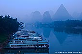 landscapes stock photography | Early Morning on Li River Near Yangshuo, Yangshuo, China, Image ID CHINA-YANGSHUO-XINGPING-0005. A picture of early misty morning on Li River (Lijiang River) near Yangshuo city in Guangxi province in China. Recreational cruise boats awaiting tourists for cruises on crystal-clear waters of Li River that twists and turns between magnificent and beautiful carst mountains.