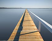 landscapes stock photography | Long Jetty, Tuggerah Lake, Central Coast, NSW, Australia, Image ID AU-NSW-LONG-JETTY-0001. Long Jetty is appropriately named as it features 3 extremely long jetties spanning out over the shallow waters of Tuggerah Lake: Parrys Jetty, Walkins Jetty and Long Jetty. The jetty was first built in 1915 and has become the namesake of the town of Long Jetty. The public artworks are a showcase of the history of the area - the pioneers who built the jetty and the local community, plus the many generations of visitors who spent time on and around Tuggerah Lake.