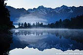 landscapes stock photography | Dawn at Lake Matheson, Lake Matheson, South Westland, South Island, New Zealand, Image ID NZ-LAKE-MATHESON-0003. Morning fog rising above Lake Matheson and Mount Cook and Mount Tasman reflect in the lake near Fox Glacier, Westland, Tai Poutini National Park, South Island, New Zealand. Lake Matheson is an ideal location for the scenic picture postcard. It's a small lake surrounded by trees. That means it is almost always has still, flat water surface - exactly what you need for reflections. It also has a view out over the tallest section of the New Zealand's Southern Alps - with Mt Cook (Aoraki) and Mt. Tasman. So it's the perfect spot for a nice picture of the distant snow-capped mountains with reflection in the still water.