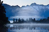 landscapes stock photography | Dawn at Lake Matheson, Lake Matheson, South Westland, South Island, New Zealand, Image ID NZ-LAKE-MATHESON-0005. Early morning mist over Lake Matheson near Fox Glacier township, located in Westland National Park on West Coast of the South Island of New Zealand and the second highest peak in New Zealand - Mt. Tasman (3,497m) as the backdrop. Lake Matheson is one of the most photographed lakes on the west coast.