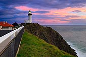 stock photography | Storm Clouds above Cape Byron Lighthouse at Sunrise, Byron Bay, New South Wales (NSW), Australia, Image ID AU-BYRON-BAY-LIGHTHOUSE-0001. The Cape Byron Lighthouse is located on the Cape Byron, Australia's the most easterly point of the mainland, near Byron Bay town. Cape Byron lighthouse was built in 1901 and for a century alerted passing ships to the dangers of the coast. In 1956 the light became Australia's most powerful lighthouse. Byron Bay Lighthouse has become an icon for Byron Bay and is a must for any visitor to Byron Bay. Take an early-morning walk to see the sun come up over the Pacific, and watch the pink glow on the lighthouse turn to stark white in the morning sun.