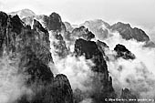 portfolio stock photography | Clouds Covered Huangshan Peaks, Cloud-dispelling Pavilion, Xihai (West Sea) Grand Canyon, Baiyun Scenic Area, Huangshan (Yellow Mountains), China, Image ID CHINA-BW-0001. Black and white photo of the cloud formations hover around the Huangshan mountain range and above the forest in Anhui Province of China.