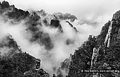 portfolio stock photography | Huangshan Mountains in Clouds, Cloud-dispelling Pavilion, Xihai (West Sea) Grand Canyon, Baiyun Scenic Area, Huangshan (Yellow Mountains), China, Image ID CHINA-BW-0003. Black and white photo of the cloud formations hover around the Huangshan mountain range and above the Xihai (West Sea) Canyon in Anhui Province of China.