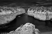 portfolio stock photography | Loch Ard Gorge in Black and White, The Twelve Apostles, Great Ocean Road, Port Campbell National Park, Victoria, Australia, Image ID GREAT-OCEAN-ROAD-BW-0006. The Loch Ard Gorge is part of Port Campbell National Park, Victoria, Australia, about three minutes' drive west of The Twelve Apostles. The gorge is named after the clipper ship Loch Ard, which ran aground on nearby Muttonbird Island on 1 June 1878 approaching the end of a three-month journey from England to Melbourne. Of the fifty-four passengers and crew, only two survived: Tom Pearce, at 19 years of age, a ship's apprentice, and Eva Carmichael, an Irishwoman emigrating with her family, at 19 years of age. According to memorials at the site, Pearce was washed ashore, and rescued Carmichael from the water after hearing her cries for help. Pearce then proceeded to climb out of the gorge to raise the alarm to local pastoralists who immediately set into plan a rescue attempt. After three months in Australia Carmichael returned to Europe. Four of her family members drowned that night. Pearce was hailed as a hero, and continued his life living until age 49. He is buried in Southampton, England.