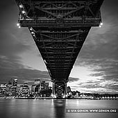 portfolio stock photography | Under The Harbour Bridge, Sydney, New South Wales (NSW), Australia, Image ID SYDNEY-IN-SQUARE-0003. Beautiful black and white photo of the Sydney Harbour Bridge steel structures and Sydney city at night, shot right from under the bridge at Milsons Point in Sydney, New South Wales, Australia.