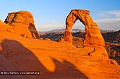 portfolio stock photography | Delicate Arch at Sunset with background of La Sal Mountains, Arches National Park, Utah, USA, Image ID AMERICAN-SOUTHWEST-0005. Delicate Arch at with background of La Sal Mountains in Arches National Park, Utah, USA is one of Utah's most famous icons. You see images of it everywhere - on magazine covers, computer screen savers and license plates. But photos do not adequately convey the stunning beauty that hits you as you come over the ridge and see the arch in person for the first time-when you stand under it, the arch towering above your head, slickrock canyons falling away below you, the snow-covered La Sal Mountains in the distance. It is a spectacular sight.