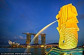 singapore stock photography | The Merlion and Marina Bay Sands Hotel at Sunset, Marina Bay, Singapore, Image ID SINGAPORE-0005. Merlion Park houses a Singapore icon that is half-fish and half-lion, and famous throughout the world. The body symbolises Singapore's humble beginnings as a fishing village when it was called Temasek, meaning 'sea town' in Old Javanese. Its head represents Singapore's original name, Singapura, or 'lion city' in Malay. Today, you can glimpse this legend at Merlion Park. Spouting water from its mouth, the Merlion statue stands tall at 8.6 metres and weighs 70 tonnes. This icon is a 'must-see' for tourists visiting Singapore, similar to other significant landmarks around the world. Built by local craftsman Lim Nang Seng, it was unveiled on 15 September 1972 by then Prime Minister Lee Kuan Yew at the mouth of the Singapore River, to welcome all visitors to Singapore.
