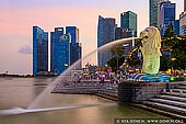 stock photography | The Merlion at Sunset, Marina Bay, Singapore, Image ID SINGAPORE-0002. The Merlion statue and city skyline of Central Financial District along Singapore River at sunset. The Merlion is the mythical creature with the head of a lion and the body of a fish. The body symbolises Singapore's humble beginnings as a fishing village when it was called Temasek, meaning 'sea town' in Old Javanese. Its head represents Singapore's original name, Singapura, or 'lion city' in Malay.